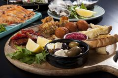 Platters of food. Anti pasta platter, tasting board with seafood in background Stock Images