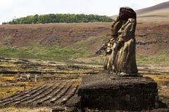 Plattform moai mot bergig grön bakgrund Fotografering för Bildbyråer