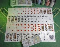 Plattform von Spielkarten, von Kasinochips und von Satz 100s von US-Dollars auf der grünen Tabelle für den Blackjack beleuchtet lizenzfreies stockbild