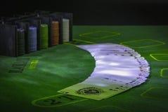 Plattform von Spielkarten und von Kasinochips auf der grünen Tabelle für den Blackjack beleuchtet mit Parteilichtern stockfoto
