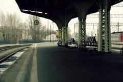 Plattformklocka och bänkar utan folk och inget drev Arkivbild