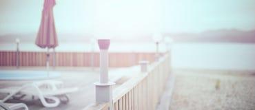Plattformstrandseeozeanerholungsortsonnenruhesesselregenschirmhotelpool-Himmelsonnenaufgang Defocus-Fahne hölzerner stockfoto