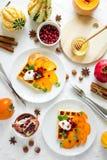 Plattor av belgiska dillandear med persimonet, granatäpplefrö och gräddfil arkivfoto