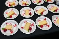 Plattor av den gula kakan med den vita glasyr på kaka- och hallongarneringen royaltyfri fotografi