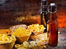 Plattor med mellanmål nära två flaskor av öl, vete, spridde nu Arkivfoton