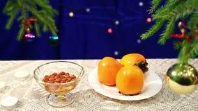 Plattor med muttrar, honung med persimoner är på tabellen på en bakgrund för ` s för nytt år med en dekorerad julgran och herders arkivfilmer