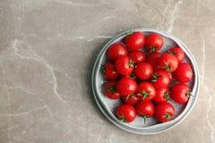 Plattor med nya mogna tomater på grå bakgrund, bästa sikt Arkivbild