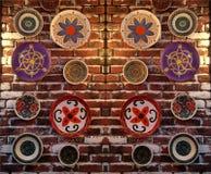 Plattor med olika modeller på en tegelstenvägg Arkivfoton