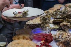 Plattor med ostron i händerna av besökare royaltyfria foton
