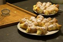 Plattor med vaniljsåskrämrullar som strilas med pudrat socker royaltyfri bild