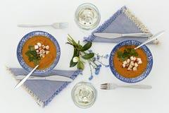 Plattor och exponeringsglas, romantisk matställe för två orange soup Fotografering för Bildbyråer