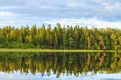 Platz für Seelenfriedenn, ein Haus im Wald und ein Boot auf dem See Lizenzfreie Stockfotografie