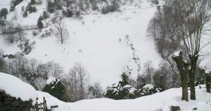 Platz zwischen den Bergen bedeckt durch Schnee mit Bäumen herum stock footage