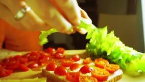 Platzierung des Blattes des frischen grünen Salats auf ein Sandwich stock footage