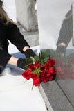 Platzierung von Blumen auf ein Grab Stockbild