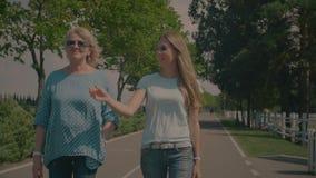 Plaudernde ältere Mutter- und Erwachsentochter, die in Park geht