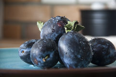 Plaums on the plate indoor. Picture of fresh plums on plate indoor Royalty Free Stock Image