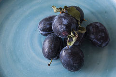 Plaums on the plate indoor. Picture of fresh plums on plate indoor Royalty Free Stock Photos
