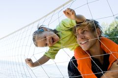 Play. Little girl laughing on young man neck and looking at camera through volleyball net Stock Photography