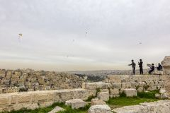 Play in Amman. AMMAN, JORDAN - MARCH 12, 2019: Four children play with home-made kites on the walls of the ancient citadel of Amman, with the old city in the stock photos