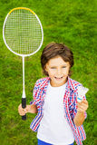 Play badminton?. Top view of happy little boy holding badminton racket and shuttlecock while standing on green grass Stock Photo