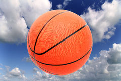 Play ball. Orange basketball up in a cloudy blue sky Stock Images