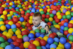 Play in balls. Happy child playing in balls Royalty Free Stock Photo