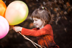 Play with baloons. Red haired girl play with colored baloons in the autumn royalty free stock photos