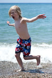 Play on beach. Young boy running in water Royalty Free Stock Image