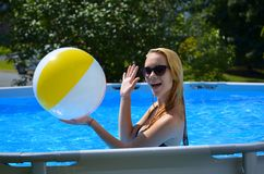 Play beachball. Teen girl ready to play a game in the family pool Royalty Free Stock Photos