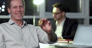 Play with bitcoin. Footage of analytic manager sitting on chair in office. Demonstrating bitcoin, a present of abroad partners. Crypto currency concept stock footage