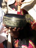 Play That Bowl. Devotee playing a ceremonial Tibetan Singing Bowl stock photo