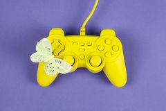 Play with butterfly in yellow and blue. A yellow painted video game controller and a yellow butterfly on it on a plain purple background. Minimal color still stock photos