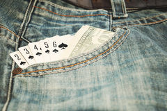 Play card Straight Flush and money in  jean pocket. Play card Straight Flush and money in the blue jean pocket Royalty Free Stock Photo