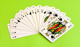 Play cards. All the spades isolated on green background. Stock Image