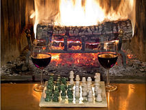 Play chess drinking red wine in front of roaring fireplace. Play chess drinking red wine in front of a roaring fireplace Royalty Free Stock Images