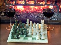 Play chess drinking red wine in front of a roaring fireplace. Play chess drinking red wine in front of roaring fireplace Stock Image