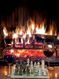Play chess drinking red wine in front of a roaring fireplace Royalty Free Stock Image