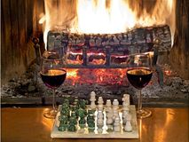 Play chess drinking red wine in front of a roaring fireplace Royalty Free Stock Photo