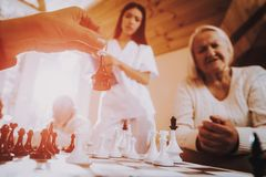 Play Chess. Nurse. Stand Nearby. Sitting Woman. Happy old family time together. Aged men play with old woman. game with family. Old wife with young nurse. Love royalty free stock photo