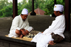 Play chess in the temple. Keeper of temple spend spare time playing chess in the temple, After the ceremony on Imlek day,Mother Temple in in Bali, Indonesia royalty free stock photos