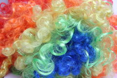 The play of colors. Color circus wig in the background Royalty Free Stock Images