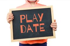 Play Date subject depicted with child holding blackboard. Play Date subject depicted with child holding blackboard with text royalty free stock image