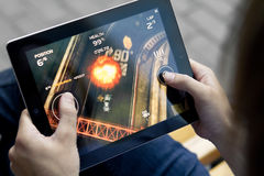 Play Death Rally on Apple Ipad2. A man outdoors play in the game Death Rally on Apple Ipad2 Stock Image