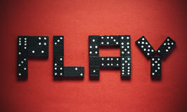 Play Dominoes. Word play written of plastic black dominoes, on red background Royalty Free Stock Image