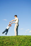 Play with father 7. Young boy played with father. Green grass. Blue sky. 7 Royalty Free Stock Photos