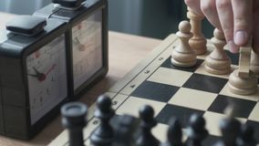 Play for a while. In the frame of the board and the clock. A man makes a move with a white horse and presses the clock button to stop the timer stock video