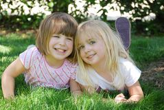 Play Fun. Two little girls laying in grass Royalty Free Stock Photo