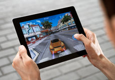 Play Game on Apple Ipad2. A man outdoors play in the game Asphalt 6 on Apple Ipad2 Stock Photography