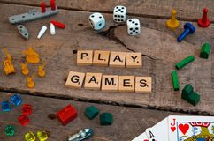 `Play Games` made from Scrabble game letters. Risk, Battleship pieces, Monopoly, Settler of Catan and other game pieces royalty free stock images